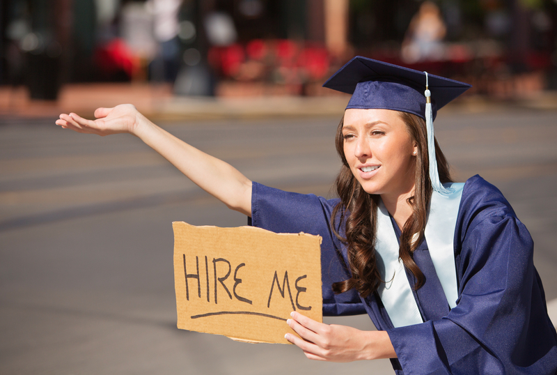 college graduate waiting to be hired with a hire me sign